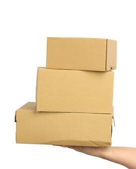 A mão segura uma caixa de papelão marrom sobre um fundo branco isolado, movendo o conceito