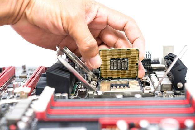 A mão segurando a cpu mostra a superfície ic e tem a montagem do soquete aberto da placa-mãe para a cpu isolada no fundo branco