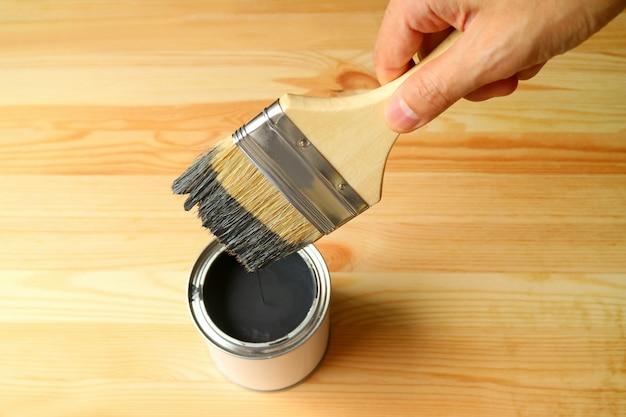A mão segurando o pincel com a tinta caindo após mergulhar na lata de tinta