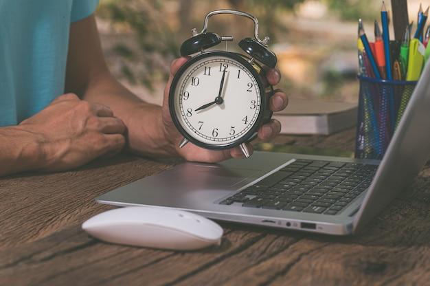 A mão segurando o relógio está na mesa de trabalho
