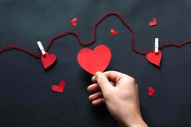 A mão segurando um coração preto sobre fundo preto, dia dos namorados. configuração plana
