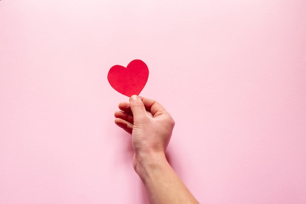 A mão segurando um coração sobre parede rosa, dia dos namorados. configuração plana