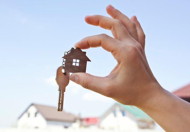 A mão segurando uma casa em miniatura com uma chave