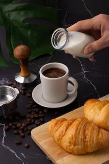 A mão segurava uma garrafa de leite, despejando-o em uma xícara de café branco, croissant em uma tábua de corte, grãos de café e um moedor de café em um piso de mármore preto.