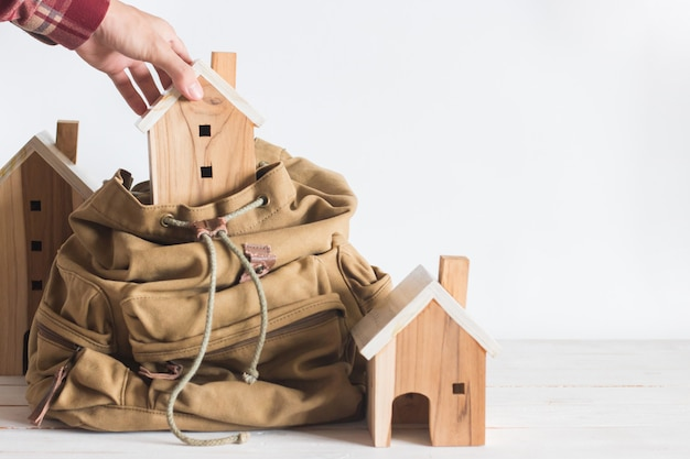 A mão toma o modelo diminuto da casa na trouxa marrom da cor, conceito do investimento da propriedade, copyspace,