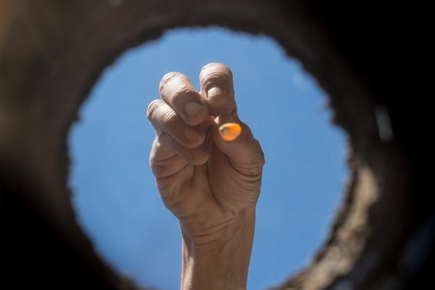 A mão trabalhadora que cultiva o jardim visto de dentro da terra