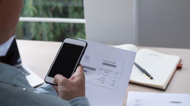 A mão usa o telefone para digitalizar o código qr e receber um desconto no pagamento de contas de energia elétrica no escritório