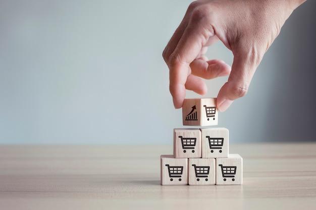 A mão vira o cubo com o gráfico de ícones e o aumento do volume de vendas do símbolo do carrinho de compras faz o negócio crescer