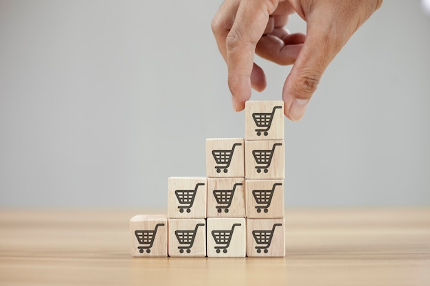 A mão vira o cubo com o ícone do símbolo do carrinho de compras para aumentar o volume de vendas e fazer o negócio crescer