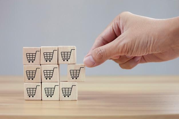 A mão vira o cubo com o símbolo do ícone do carrinho de compras