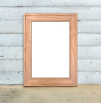 A maquete vertical do quadro de madeira a4 velho está em uma tabela de madeira em um fundo de madeira branco pintado. estilo rústico, beleza simples. 3d rendem.