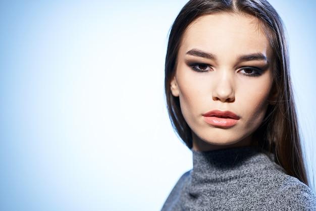 A maquiagem brilhante de mulher atraente alisa o cabelo com modelo elegante de mão