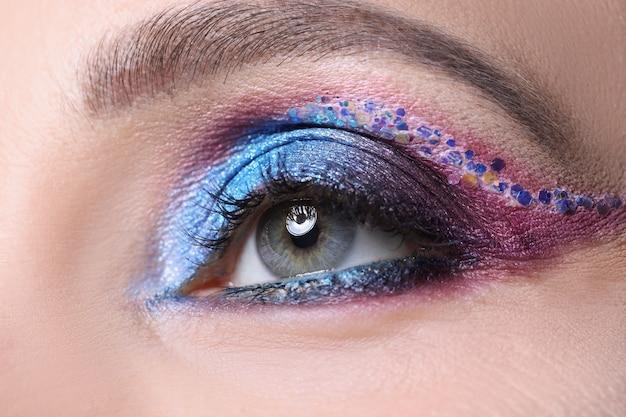 A maquiagem dos olhos multicoloridos brilhantes para mulheres brilha e reluz no conceito de maquiagem