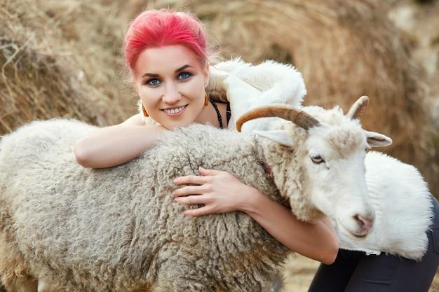 A maquiagem vermelha brilhante da mulher no rosto abraça a ram com chifres. maquiagem criativa de rosa quente no rosto de menina, coloração de cabelo. retrato de uma menina com uma ovelha. andar na floresta de outono. roupas de lã de outono