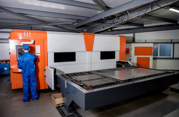 A máquina de corte a laser cortando a folha de metal.