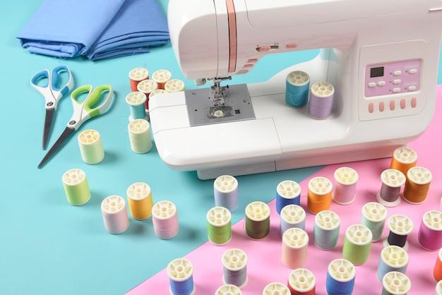 A máquina de costura e a linha colorida rolam para o conceito da costura, da costura e do bordado.
