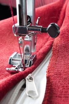 A máquina de costura moderna costura o zíper de uma peça de roupa vermelha. processo de costura
