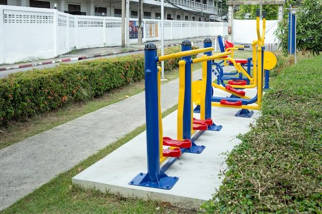 A máquina de exercício amarela, vermelha e azul no parque próximo à estrada.