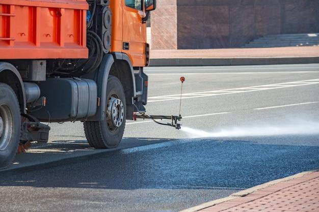 A máquina de limpeza lava a superfície da estrada asfaltada na rua da cidade.