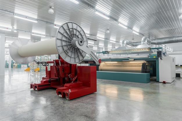 A máquina hidráulica de elevação levanta grandes bobinas. têxtil e fiação