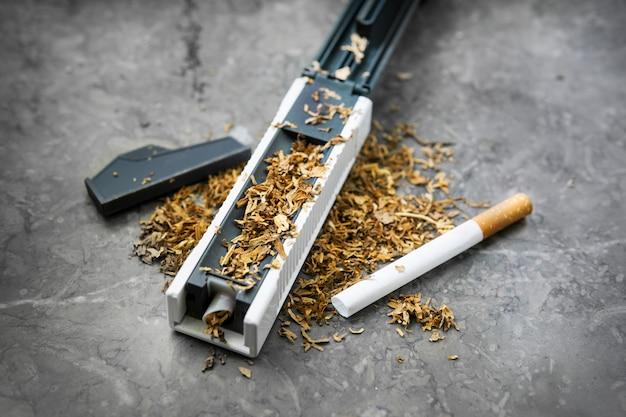 A máquina para encher cigarros com tabaco. suspiro vazio. tabaco rossypany em cima da mesa. produção de cigarros caseiros