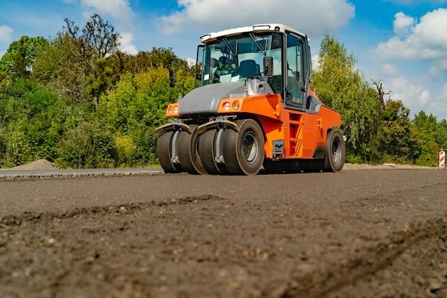 A maquinaria de construção para trabalhos de estrada passa através do asfalto novo no verão das árvores
