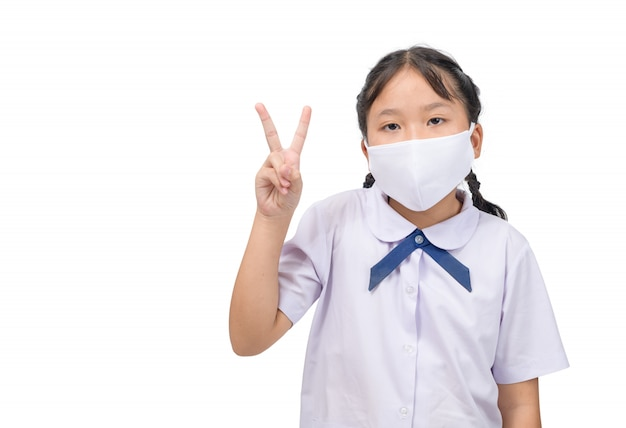 A máscara asiática do desgaste da menina do estudante contra o vírus infeccioso e mostra a vitória assina as mãos isoladas no branco.