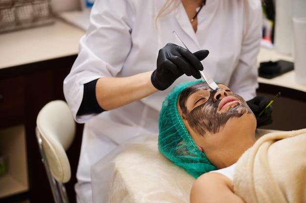 A máscara cosmética preta é aplicada no rosto do paciente com uma escova e espátula