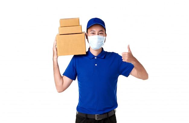 A máscara protetora vestindo asiática do homem de entrega no uniforme azul que está com leva a caixa do cargo do pacote isolada sobre o fundo branco. serviço de entrega expressa durante covid19.