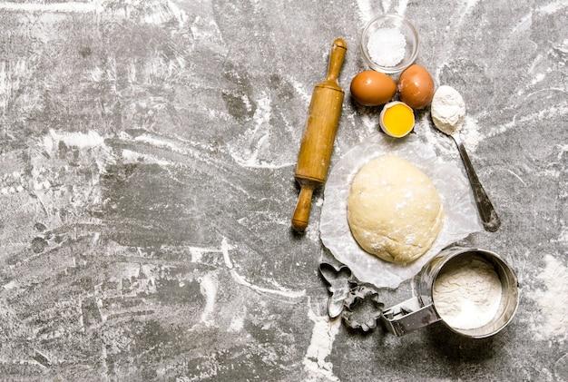 A massa e os ingredientes - ovos, farinha e ferramentas - um rolo de massa e uma forma. na mesa de pedra. espaço livre para texto. vista do topo