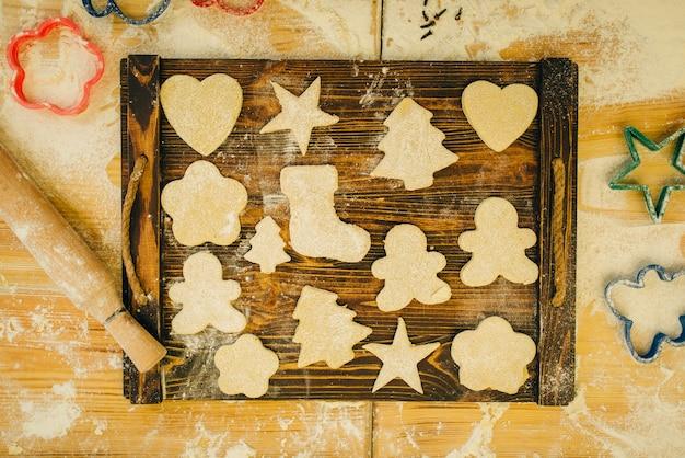 A massa em diferentes formas cortadas por cortadores de biscoitos na placa de madeira, vista de cima, ninguém. corações, estrelas e boneco de gengibre, modelos de pastelaria na mesa