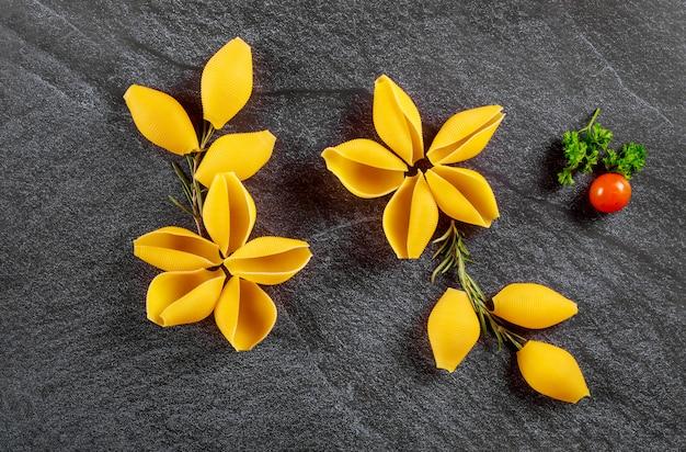 A massa seca dos escudos gosta de uma flor com tomate no fundo preto.