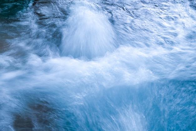 A massagem da água jorrando rapidamente na piscina azul.