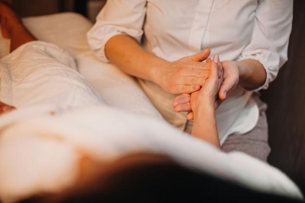 A massagista caucasiana cuidadosa massageia a mão da cliente enquanto ela está deitada no sofá durante um procedimento de spa