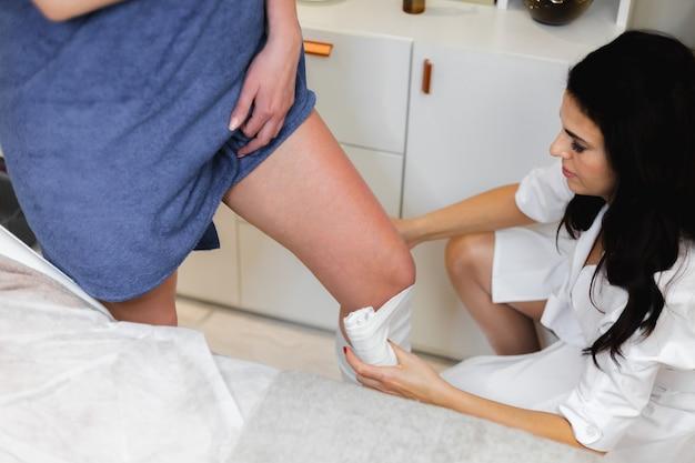A massagista do salão de beleza do spa envolve a cliente para deixar o corpo em forma e se livrar do inchaço