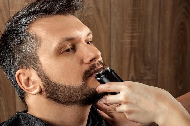 A master corta os pelos do nariz para o cliente com um aparador, close-up. o processo no cabeleireiro, barbearia. cuidado corporal, estilo de vida, metrossexual.