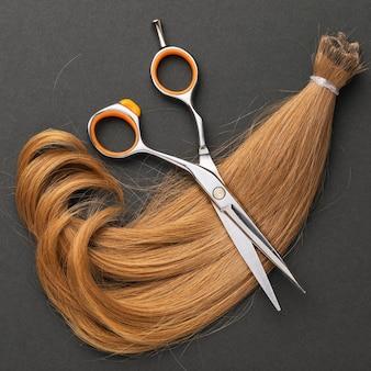 A mecha cortada do cabelo feminino das crianças é castanho claro em uma superfície escura vista superior serviços de cabeleireiro