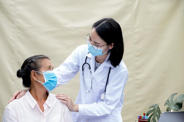 A médica apóia os pacientes nos ombros dos idosos e orienta os cuidados de saúde amigáveis