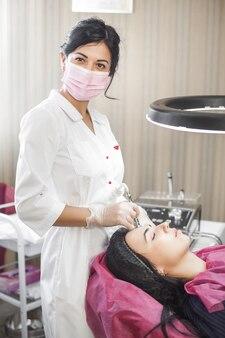 A médica está fazendo um procedimento de microdembrasão em seu paciente. cuidados com o rosto. cosmetologista fazendo peeling de aparelhos, esfoliação. feche ainda mais o tratamento de pele na clínica de beleza ou no salão de beleza.