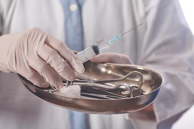 A médica está preparando a seringa para injetar o paciente na sala de exames.