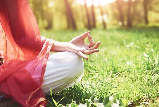 A meditação de ioga em um parque na grama é uma mulher saudável em repouso.