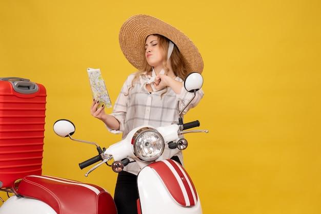 A melhor competição de uma jovem orgulhosa usando um chapéu, recolhendo sua bagagem, sentada em uma motocicleta e segurando o mapa