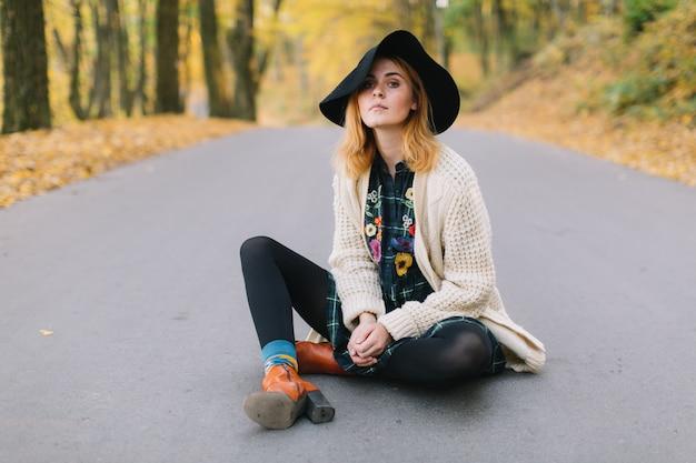 A menina à moda da hippie em uma camiseta e em um chapéu feitos malha anda no parque do outono.