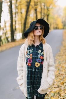 A menina à moda da hippie em uns óculos de sol, camiseta e chapéu feitos malha anda no parque do outono.