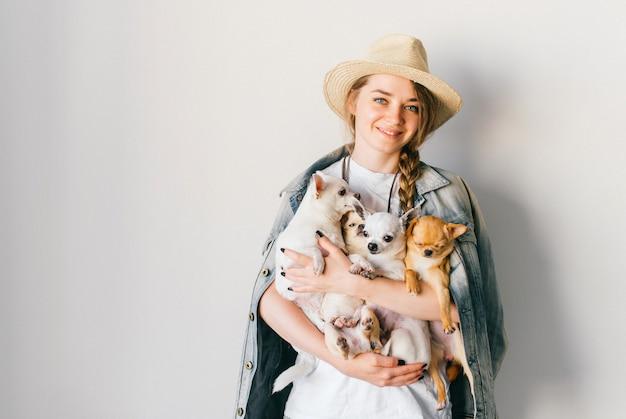 A menina à moda nova de sorriso feliz que guarda quatro filhotes de cachorro adoráveis da chihuahua nela cede a parede branca.