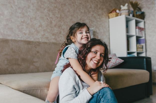 A menina abraça a mãe feliz pelo pescoço e sorri alegremente juntas. um grande retrato. feliz maternidade