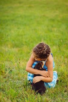 A menina abraça cachorrinho sentado no campo