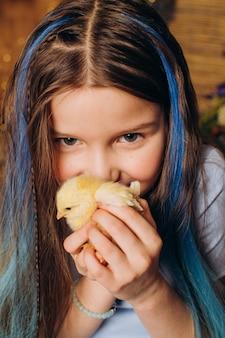 A menina abraça o frango conceito de férias de páscoa e ecologia