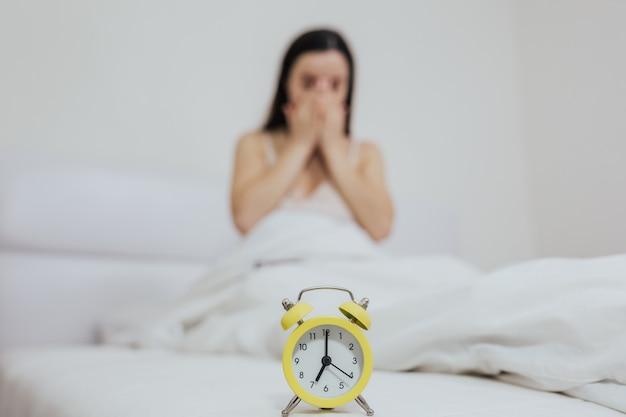 A menina acorda de manhã bocejando com os olhos fechados enquanto está sentada na cama