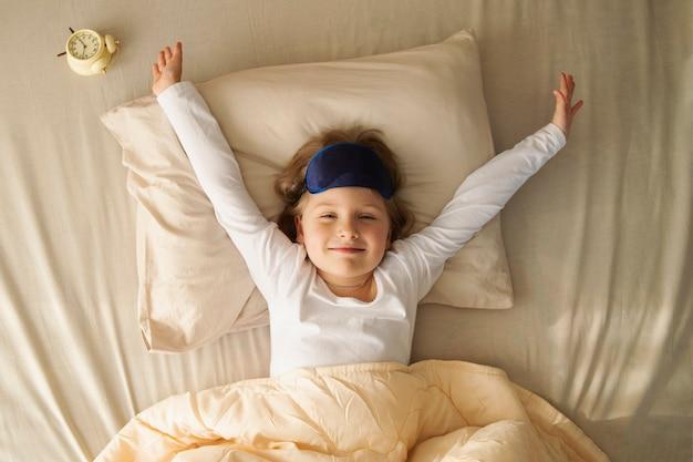 A menina acordou de bom humor alongando eu dormi bem é hora de levantar e bom dia sono saudável